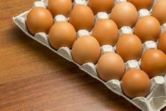 Kippeneieren in een mand onder het hooi Stock Afbeeldingen