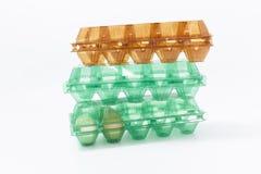 Kippeneieren in een plastic container op een witte achtergrond Stock Afbeelding