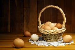 Kippeneieren in een rieten mand op een houten lijst royalty-vrije stock foto's