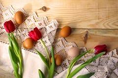 Kippeneieren, rode tulpen op een wit gehaakt tafelkleed royalty-vrije stock foto
