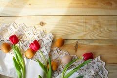 Kippeneieren, rode tulpen op een wit gehaakt tafelkleed stock fotografie