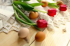 Kippeneieren, rode tulpen op een wit gehaakt tafelkleed royalty-vrije stock foto's