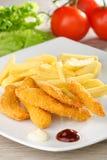 Kippengoudklompjes/kleverige vingers met frieten Stock Afbeeldingen