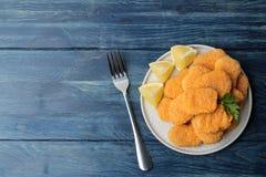 kippengoudklompjes op een plaat met vork met citroenplakken op een blauwe houten lijst Hoogste mening met ruimte voor tekst stock afbeelding
