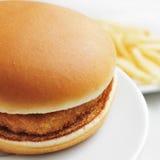 Kippenhamburger en gebraden gerechten Royalty-vrije Stock Afbeeldingen