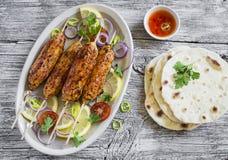 Kippenkebabs op houten vleespennen op een ovale plaat en een eigengemaakte tortilla Stock Fotografie