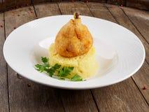 Kippenkotelet op een been met fijngestampte aardappels en een blad van peterselie royalty-vrije stock afbeeldingen