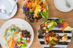 Kippenlapje vlees, gebakken spinazie met kaasroti, en salade op een houten lijst stock foto's