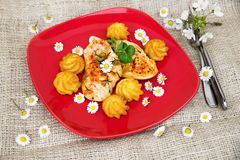 Kippenlapje vlees, gebraden aardappelmand en lentetijdbloemen Stock Foto's