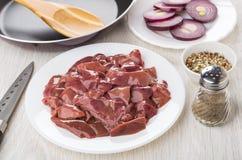Kippenlever, specerij, peper, rode ui, pan en knif royalty-vrije stock foto's