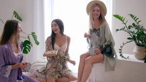 Kippenpartij, dames die in zijdebadjassen met koppen van koffie en doos van suikergoed bij slaapkamer roddelen stock video