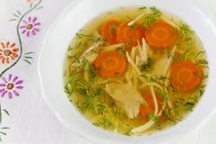Kippensoep of bouillon met noodels, de stukken van het kippenvlees, wortelplakken en kruiden Stock Foto