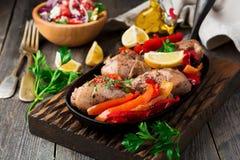 Kippentrommelstokken met gebakken peper en citroen in een pan op een donkere achtergrond Stock Foto's