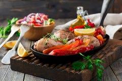 Kippentrommelstokken met gebakken peper en citroen in een pan op een donkere achtergrond Stock Foto