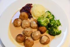 Kippenvleesballetjes en Aardappel en broccoli en romige jussaus in de schotel op de houten achtergrond, klassiek recept, close-up stock afbeelding