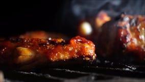 Kippenvleugels die met honing op een barbecue bij nacht roosteren stock videobeelden