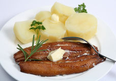 Kipper and potatoes. A kipper, or smoked herring, served with boiled potatoes and a knob of butter Royalty Free Stock Photo