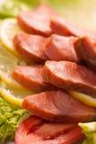Kipper slices. With lemon and lettuce macro photo Stock Photos