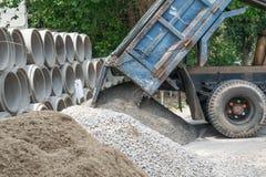 Kipplaster, der Sand an der Baustelle entlädt Lizenzfreie Stockfotos