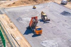 Kipplaster entlädt Asphalt an der Baustelle des Schulstadions Stockbild