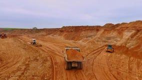 Kipwagenvrachtwagen die zand in steengroeve vervoeren Luchtmening van het zandwerk stock footage