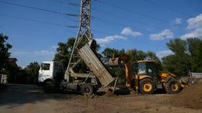Kipwagenvrachtwagen het leegmaken grond of zand bij bouwwerf tijdens de wegwerken de tractoremmer helpt om de resten leeg te make stock videobeelden