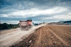 kipwagenvrachtwagens die aan wegbouwwerf, lading en het leegmaken grint en aarde werken op zwaar werk berekende machinesactivi stock afbeeldingen