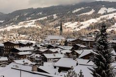 Kirchberg em Tirol, Tirol/Áustria - 26 de março de 2019: Igreja e casas na vila coberta com uma camada da lata de neve imagens de stock royalty free