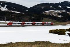 Kirchberg in Tirol, Tirol/Austria: March 28 2019: OBB public transport train driving through the snowy valley. Toward Kirchberg in Tirol royalty free stock image