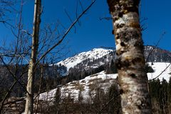 Kirchberg in Tirol, Tirol/Austria - March 24 2019: Part of the Gaisberg shot through trees and bushes whilst hiking a trail. In the valley royalty free stock photo