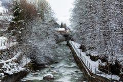 Kirchberg in Tirol, Tirol/Oostenrijk - Maart 26 2019: Rivier die door het dorp en zijn de winterlandschap vloeien stock foto