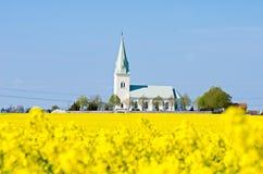 Kirche auf einem Canolagebiet Stockfoto