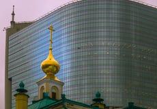 Kirche auf einem Hintergrund eines modernen hohen Gebäudes Stockfotos