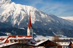 Kirche auf snow-covered Gebirgshintergrund Stockbilder