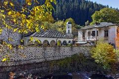 Kirche des 19. Jahrhunderts der Annahme, des Flusses und des Herbstbaums in der Stadt von Shiroka Laka, Bulgarien Lizenzfreies Stockbild