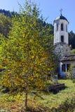 Kirche des 19. Jahrhunderts der Annahme, des Flusses und des Herbstbaums in der Stadt von Shiroka Laka, Bulgarien Lizenzfreie Stockfotografie