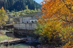 Kirche des 19. Jahrhunderts der Annahme, des Flusses und des Herbstbaums in der Stadt von Shiroka Laka, Bulgarien Lizenzfreies Stockfoto