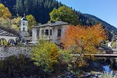 Kirche des 19. Jahrhunderts der Annahme, des Flusses und des Herbstbaums in der Stadt von Shiroka Laka, Bulgarien Stockfotos