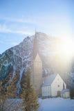 Kirche im Sonnenlichtglühen morgens in den Alpen Lizenzfreies Stockbild