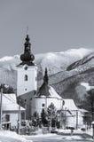 Kirche im Vordergrund- und Tempelhochgebirge voll des Schnees Stockbild