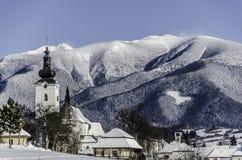 Kirche im Vordergrund- und Tempelhochgebirge voll des Schnees Stockfoto