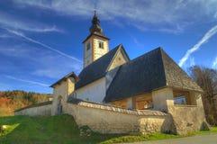 Kirche Johannes der Baptist nahe See Bohinj, Slowenien - Herbstansicht Lizenzfreies Stockfoto