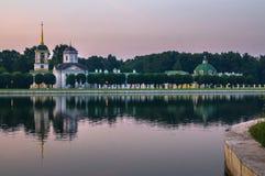 Kirche mit Glockenturm nahe bei dem Teich- und Parkpavillon ` Grotte ` im Museumzustand Kuskovo, Moskau stockfoto
