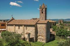 Kirche und Glockenturm mit Bäumen in Monteriggioni lizenzfreies stockbild