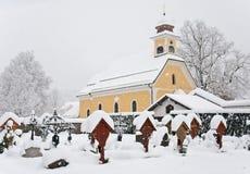 Kirche und Gräber im Winter umfasst mit Schnee lizenzfreie stockbilder