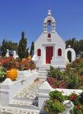 Kirche, versenkt in Blumen und in blauen Himmel Lizenzfreie Stockbilder