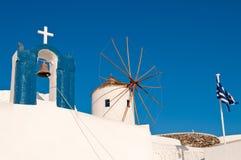 Kirche, Windmühle und griechische Markierungsfahne Stockbild