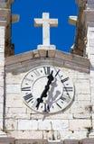 Kircheborduhr mit Kreuz Stockfotos