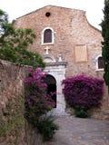 Kirchefassade mit Bouganvillablumen Stockbild