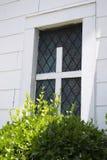 Kirchen-Fenster mit weißem Kreuz in der Mitte und in den Büschen Lizenzfreie Stockbilder